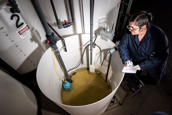 Rachel Jacobs, a chemical engineer, analyzes water in a tank in the Ballast Water Treatment Lab at Carderock