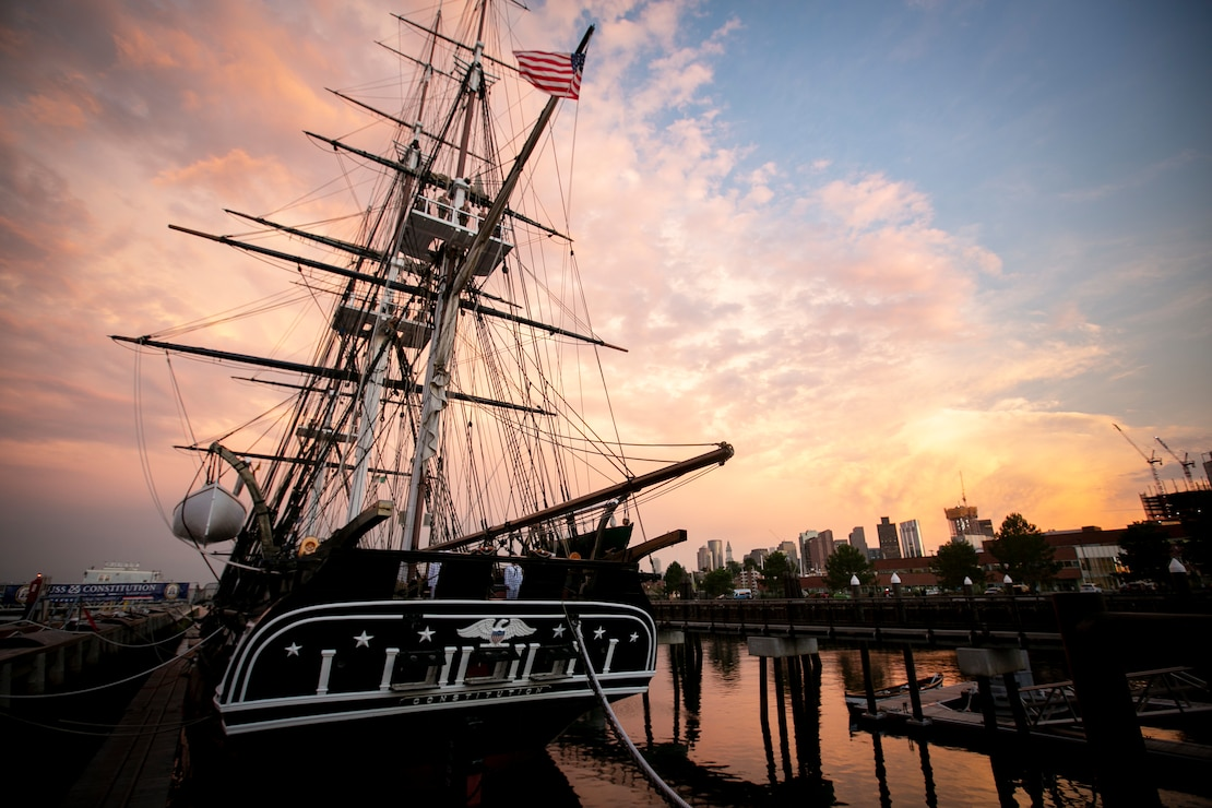 The ship is docked with beautiful sunset in the background along with Boston skyline