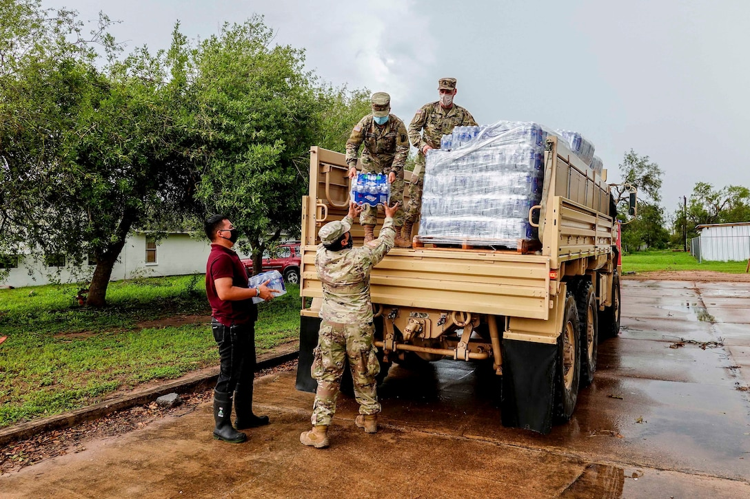 Soldiers unload packets of water from a truck.