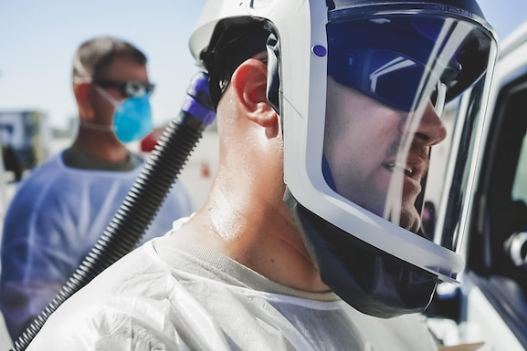 U.S. Air Force Capt. Patrick McGar, 144th Fighter Wing clinical nurse, administers a COVID-19 test at a drive-thru testing site in Indio, Calif.