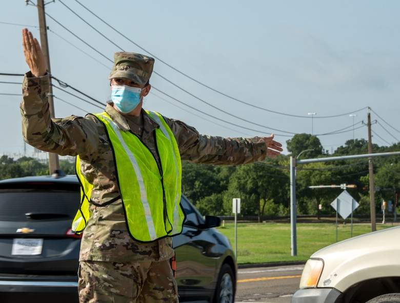 Texas Air National Guard Tech. Sgt. Brenna Jackson directs exiting traffic during a food distribution event on July 8, 2020, in Arlington, Texas.