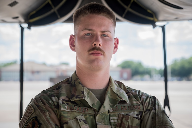 Senior Airman Kaid Hackler, 96th Aircraft Maintenance Unit aerospace propulsion journeyman, poses for a photo below the engines of a B-52H Stratofortress at Barksdale Air Force Base, La., July 23, 2020.