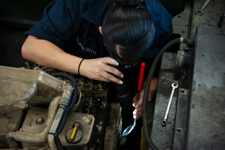 U.S. Air Force Staff Sgt. Virginia Bludworth, a 6th Logistics Readiness Squadron vehicle mechanic, uses a flashlight and inspection mirror to view the fuel injection pump on an MB-2 aircraft tow tractor, July 15, 2020, at MacDill Air Force Base, Fla.