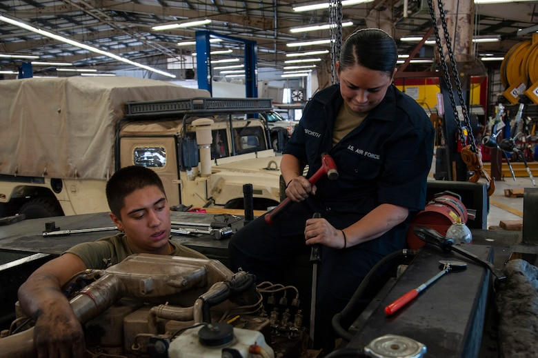 U.S. Air Force Airman 1st Class Sebastian Nucatola and Staff Sgt. Virginia Bludworth, 6th Logistics Readiness Squadron vehicle mechanics, work to access the fuel injection pump on an MB-2 aircraft tow tractor, July 15, 2020, at MacDill Air Force Base, Fla.