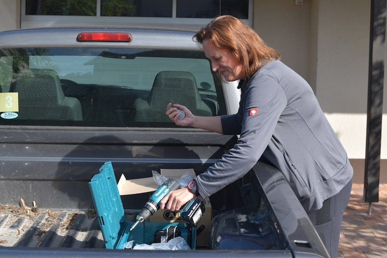 A person getting a power drill out of the back of a truck.