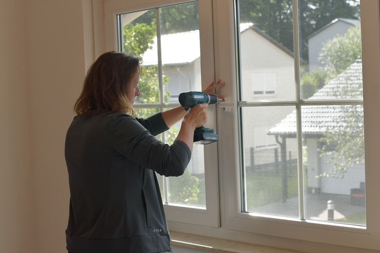 A person screwing on a window handle with a power drill.