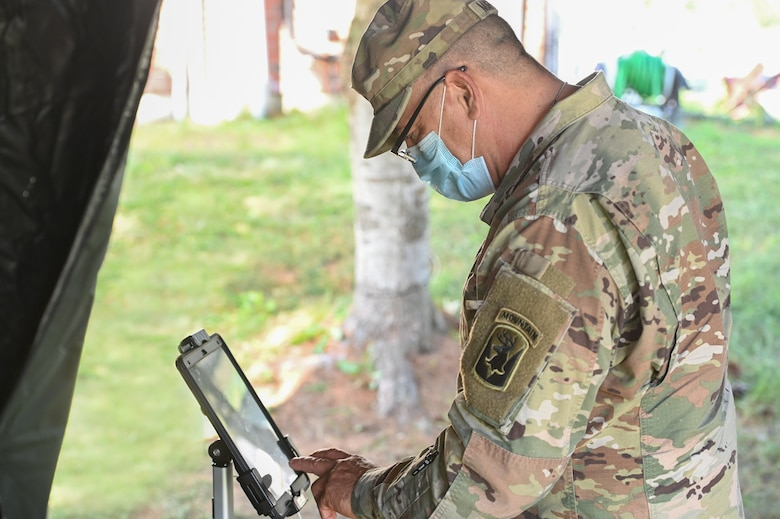 Staff Sgt. Jose Marrero, Massachusetts National Guard mechanic, creates an appointment on a tablet at the Visitor Control Center at Hanscom Air Force Base, Mass., July 29. Personnel can now join the queue and schedule VCC appointments in advance by visiting https://v2.waitwhile.com/welcome/hafbvcc.(U.S. Air Force photo by Todd Maki)