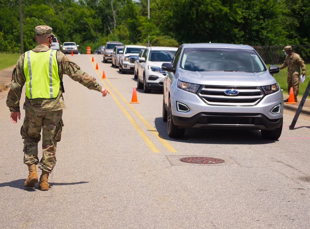 U.S. Army 1st Lt. Nicholas Barnett, 48th Infantry Brigade Combat Team, Georgia National Guard, directs traffic at a COVID-19 mobile testing site in Albany, Georgia, May 19, 2020. Soldiers and Airmen from the Georgia National Guard have been working in conjunction with Augusta University Health providing free testing of Georgia citizens to increase the testing capacity throughout the state. The site in Albany is currently one of the busiest test sites in the state. (U.S. Air National Guard photo by Senior Master Sgt. Roger Parsons)