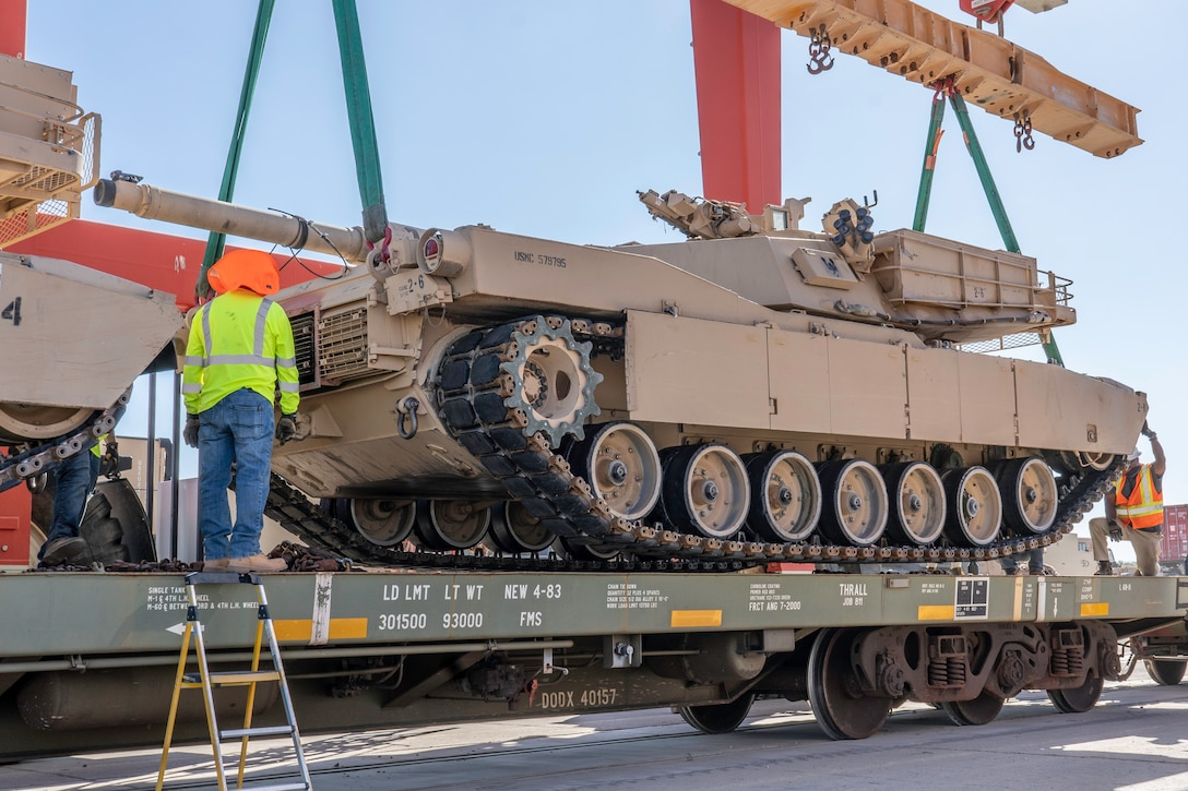 """Civilian employees use hand signals to lower the M1A1 """"Abrams"""" tank onto the rail cars aboard Marine Corps Logistics Base Barstow, Calif., July 7."""