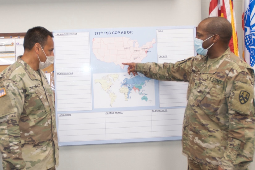 A soldier points to Texas on a wall-mounted map as another soldier looks on. Both are wearing face masks..