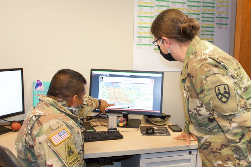 A seated soldier points out a detail on a computer monitor as another soldier standing next to him looks at the monitor. Both are wearing face masks.