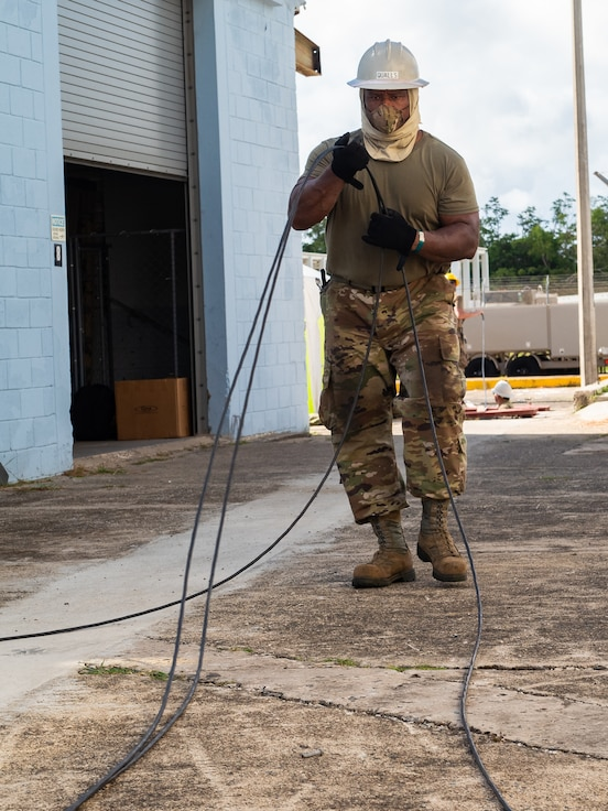 U.S. Air Force Tech. Sgt. Antonio Qualls, cable and antenna technician with the 202d Engineering Installation Squadron (EIS), 116th Air Control Wing, Georgia Air National Guard, prepares fiber optic cables for installation during a large-scale communications infrastructure project at Muñiz Air National Guard Base, Puerto Rico, July 22, 2020. The 202d EIS is leading the project which includes multiple Air National Guard EIS units. The Airmen are relocating multiple communication systems' cables and equipment to hardened facilities as part of the on-going recovery efforts in response to damage sustained during Hurricanes Irma and Maria. (U.S. Air National Guard photo by Senior Master Sgt. Roger Parsons)