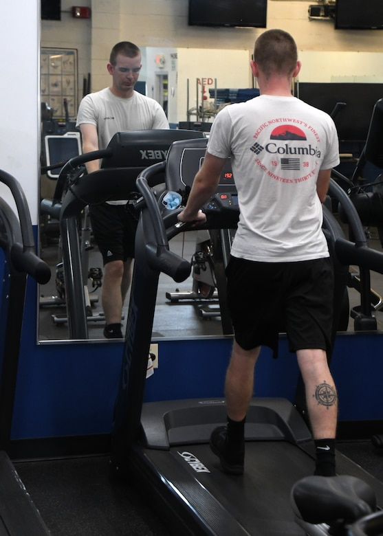 Senior Airman Brandon Ewing, 104th Fighter Wing Logistics Readiness Airman, walks on the treadmill in the base fitness room July 28, 2020, at Barnes Air National Guard Base, Massachusetts. Due to the COVID-19 pandemic, wing members who choose to work out need to sign in and follow stricter guidelines in order to maintain a safe and healthy environment.  (U.S. Air National Guard photo by Senior Airman Sara Kolinski)
