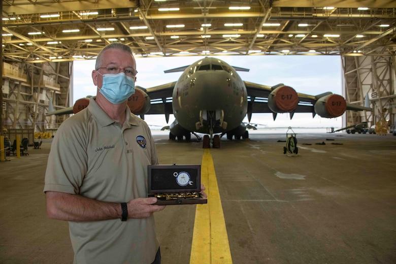 man holds award infront of aircraft