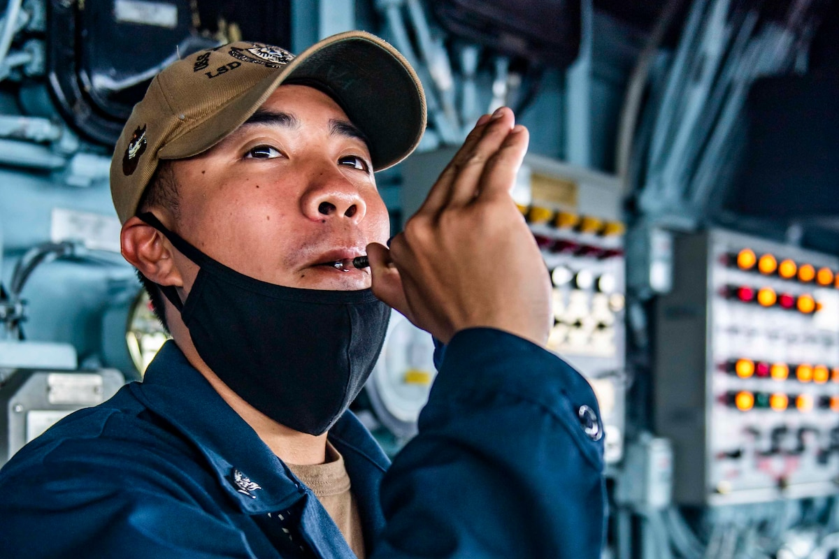 A sailor plays a signal pipe on a ship.