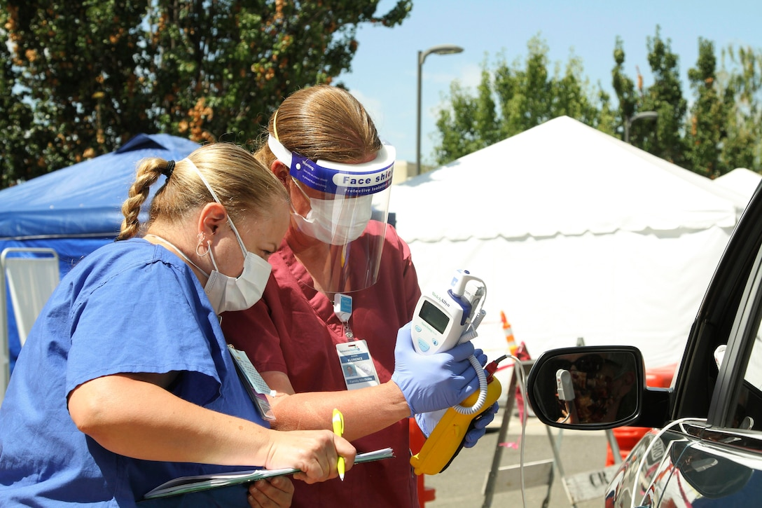 An airman and a nurse wearing protective gear talk to a motorist.
