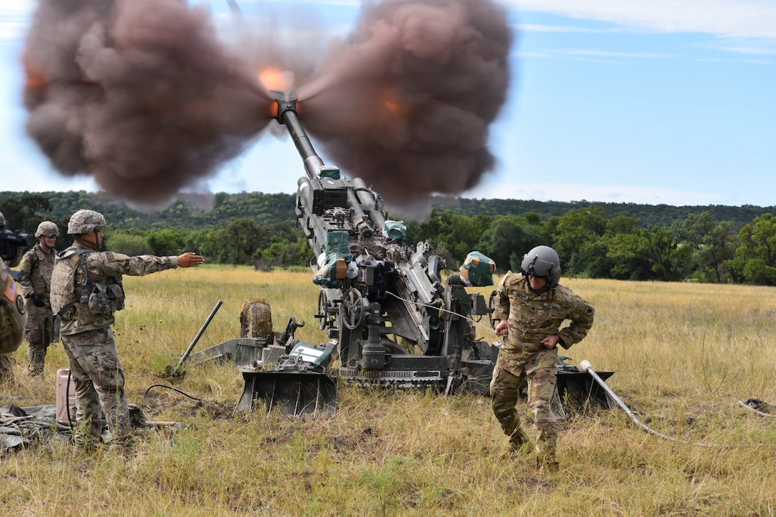 Soldiers fire a weapon in a field-like area.