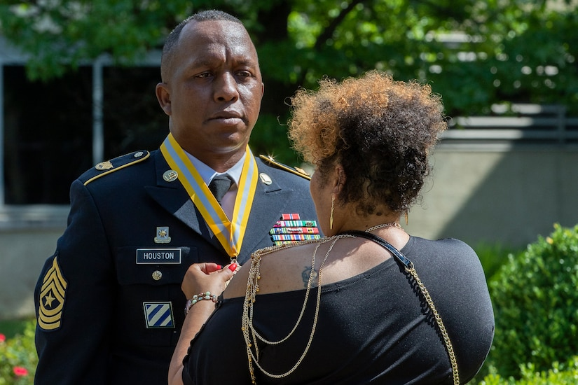 Shani Adams-Houston places a medallion around the neck of her husband, recently retired Sgt. Maj. Ronald Houston, U.S. Army Financial Management Command Operations senior enlisted advisor, shortly after he was presented with the award for being inducted as a distinguished member of the Army Finance Regiment during his retirement ceremony at the Maj. Gen. Emmett J. Bean Federal Center in Indianapolis July 17, 2020. Sergeant Major Houston was born and raised in New Orleans, Louisiana, and he joined the Army as a financial management specialist in May 1992, four days after graduating from high school. (U.S. Army photo by Mark R. W. Orders-Woempner)