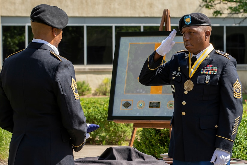 """Recently retired Sgt. Maj. Ronald Houston, U.S. Army Financial Management Command Operations senior enlisted advisor, salutes the American flag as he an Master Sgt. L. Alphanzo Hunter take part in the """"Old Glory"""" portion of Houston's retirement ceremony at the Maj. Gen. Emmett J. Bean Federal Center in Indianapolis July 17, 2020. Houston was born and raised in New Orleans, Louisiana, and he joined the Army as a financial management specialist in May 1992, four days after graduating from high school. (U.S. Army photo by Mark R. W. Orders-Woempner)"""