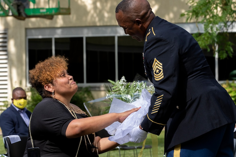 Sgt. Maj. Ronald Houston, U.S. Army Financial Management Command Operations senior enlisted advisor, presents flowers to his wife, Shani Adams-Houston, during his retirement ceremony at the Maj. Gen. Emmett J. Bean Federal Center in Indianapolis July 17, 2020. Sergeant Major Houston retired from the Army after more than 28 years of military service. (U.S. Army photo by Mark R. W. Orders-Woempner)