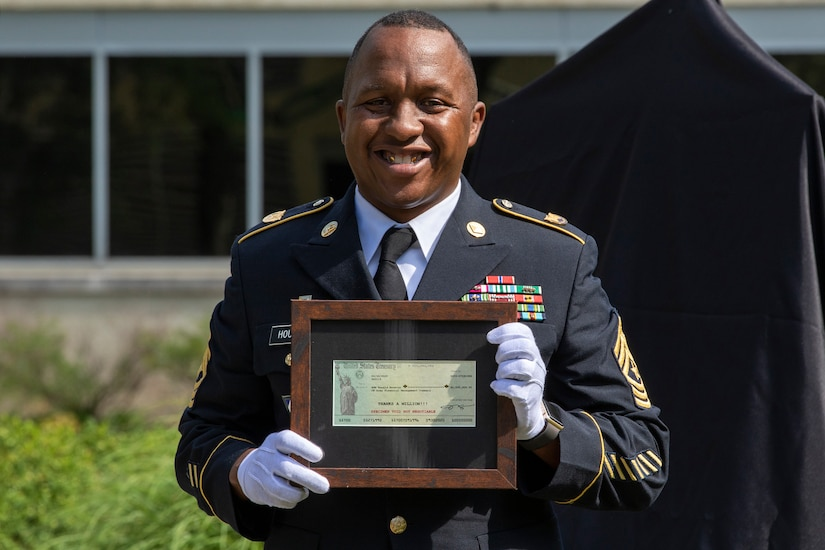"""Recently retired Sgt. Maj. Ronald Houston, U.S. Army Financial Management Command Operations senior enlisted advisor, poses with a voided U.S. Treasury check during his retirement ceremony at the Maj. Gen. Emmett J. Bean Federal Center in Indianapolis July 17, 2020. The voided check, not worth any monetary value, was made out for $1 million and was presented on behalf to of the Defense Finance and Accounting Service director with a note on it that said, """"Thanks a million!"""" (U.S. Army photo by Mark R. W. Orders-Woempner)"""