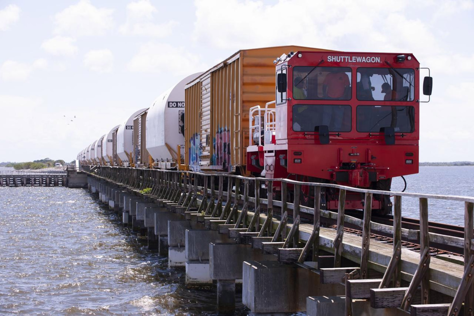 Photo of a train carrying a load over a bridge.