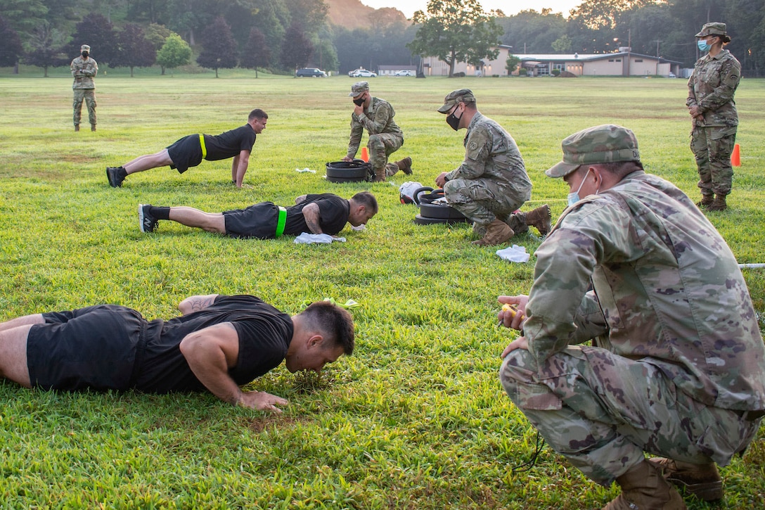Guardsmen perform pushups as other guardsmen watch wearing protective gear.
