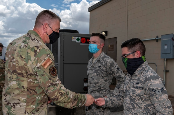 Maj. Gen. William Spangenthal, vice commander of Air Education and Training Command, coins Airman 1st Class Brian Hallock and Airman 1st Class Sebastian Flores, both from the 502nd Operational Support Squadron, during an immersion tour June 24, 2020, at Joint Base San Antonio-Lackland, Texas.