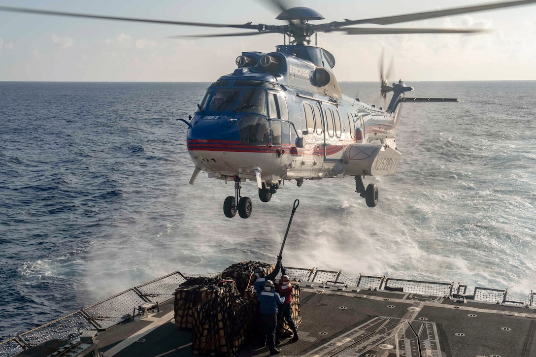 Sailors attach cargo to a helicopter while aboard a ship at sea.