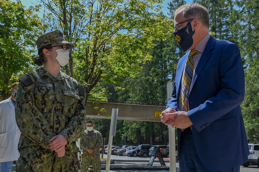 A man wearing a business suit speaks with a sailor outdoors. Both are wearing face masks.