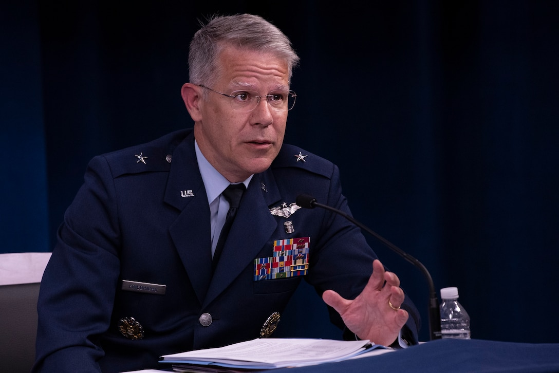 A man in military uniform sits at a table behind a microphone.