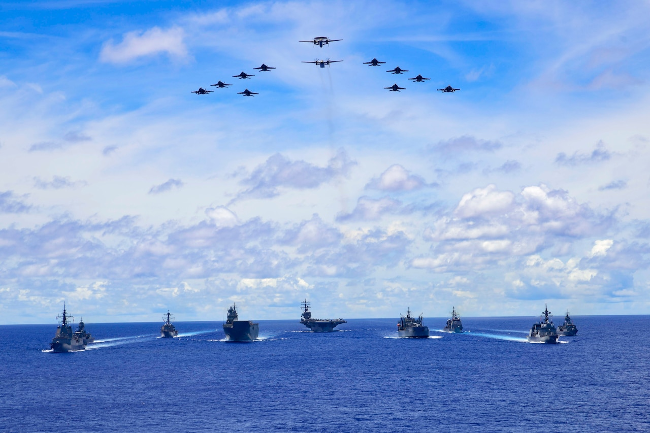 A triangular formation of aircraft flies above a formation of ships in blue sea.
