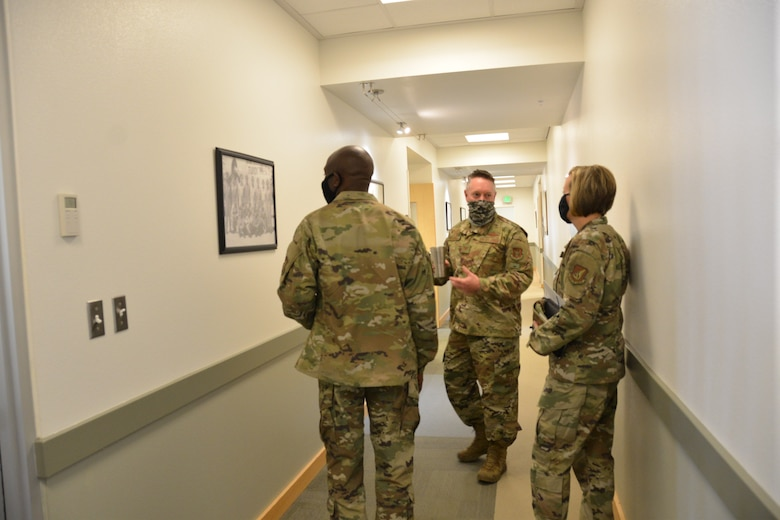 Photo of U.S. Air Force Col. Brett Paola, 477th Fighter Group commander discusses a historical World War II photo while Col. Travolis Simmons, 3rd Wing commander and Chief Master Sgt. Rebecca Bateman, 3rd WG command chief look on.