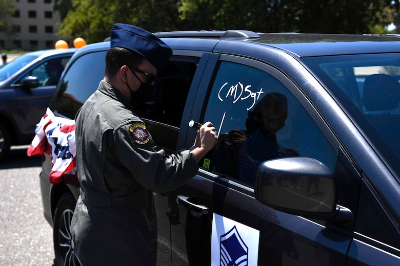 U.S. Air Force Tech. Sgt. Wes Nesting, 321st Air Mobility Operations Squadron aeromedical evacuation controller, decorates his car during a master sergeant release celebration July 23, 2020, at Travis Air Force Base, California. Travis AFB Airmen selected for promotion to master sergeant celebrated by participating in a parade in order to adhere to COVID-19 social distancing guidelines. (U.S. Air Force photo by Airman 1st Class Cameron Otte)