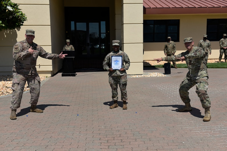 U.S. Air Force Col. Corey Simmons, left, 60th Air Mobility Wing commander, and Chief Master Sgt. Robert Schultz, right, 60th AMW command chief, recognize Tech. Sgt. Kila Archer, 621st Contingency Response Wing logistics planner and a master sergeant select, July 23, 2020, at Travis Air Force Base, California. Archer is one of 39 Airmen at Travis AFB who were selected for promotion to master sergeant July 16. The master sergeant selects grabbed their certificates from a table and posed for a photo while social distancing to mitigate the spread of COVID-19. (U.S. Air Force photo by Airman 1st Class Cameron Otte)