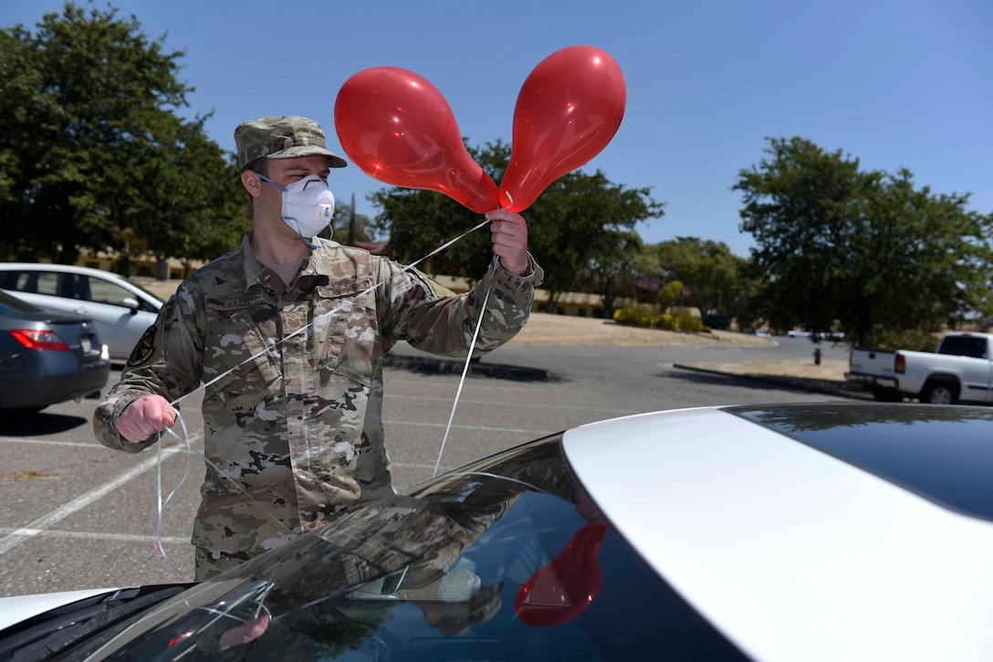 U.S. Air Force Tech. Sgt. Nicholas Tkach, 60th Operations Support Squadron aircrew flight equipment non-commissioned officer in charge, decorates his car with balloons during a master sergeant release celebration July 23, 2020, at Travis Air Force Base, California. Travis AFB Airmen selected for promotion to master sergeant celebrated by participating in a parade in order to adhere to COVID-19 social distancing guidelines. (U.S. Air Force photo by Airman 1st Class Cameron Otte)
