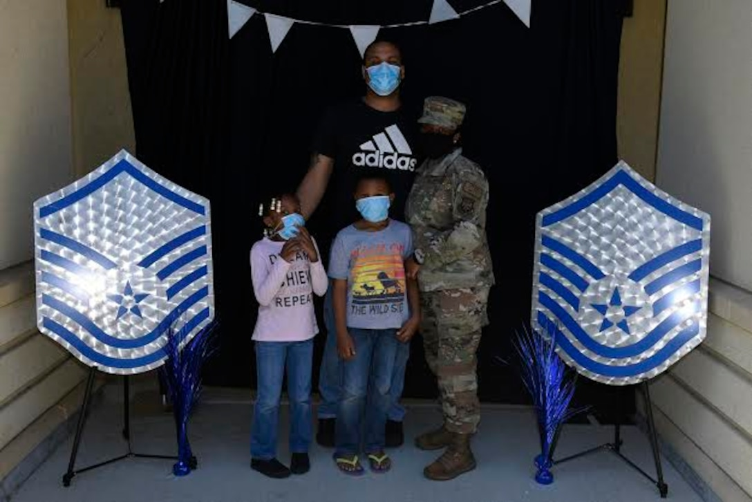 U.S. Air Force Tech. Sgt. Kila Archer, 621st Contingency Response Wing logistics planner, poses for a photo with her family during a master sergeant release celebration July 23, 2020, at Travis Air Force Base, California. The event coordinators created a photo booth for master sergeant selects and their families to take photos. (U.S. Air Force photo by Airman 1st Class Cameron Otte)
