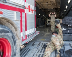 U.S. Airmen assigned to the 30th Aerial Port Squadron, Niagara Falls Air Reserve Station New York and the 22nd Airlift Squadron, Travis Air Force Base, California load a fire truck inside a C-5M Super Galaxy at Niagara Falls Air Reserve Station, New York, July 25, 2020. The aircrew transported humanitarian aid, to include a fire truck and ambulance to Nicaragua. (U.S. Air Force photo by Peter Borys)