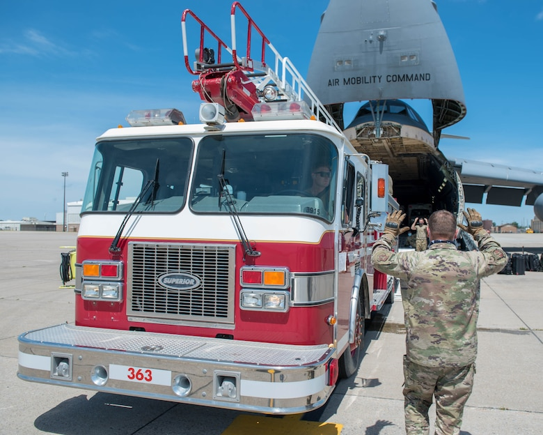 U.S. Airmen assigned to the 30th Aerial Port Squadron, Niagara Falls Air Reserve Station New York and the 22nd Airlift Squadron, Travis Air Force Base, California guide a fire truck into a C-5M Super Galaxy at Niagara Falls Air Reserve Station, New York, July 25, 2020. The aircrew transported humanitarian aid, to include a fire truck and ambulance to Nicaragua. (U.S. Air Force photo by Peter Borys)