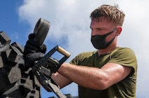 U.S Marine Corps Lance Cpl. Benjamin Boles, a motor transport operator with 3rd Marine Logistics Group, wears a face covering in support of Health Protection Conditions, as he prepares gear for delivery on Camp Kinser, Okinawa, July 29, 2020.
