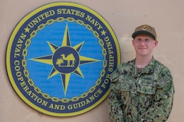 200625-N-IO414-1037 NAVAL SUPPORT ACTIVITY BAHRAIN (June 25, 2020) Ensign Michael Petty poses for a photo in front of U.S. Naval Forces Central Command's Naval Cooperation and Guidance for Shipping (NCAGS) headquarters. NCAGS serves as a communication link between merchant and military vessels and is made up entirely of U.S. Navy reservists, many of whom are professional merchant marines who leverage their civilian expertise and experience when they report for duty.
