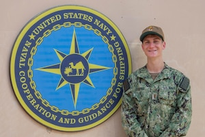 200625-N-IO414-1041 NAVAL SUPPORT ACTIVITY BAHRAIN (June 25, 2020) Ensign Jonathon Deering poses for a photo in front of U.S. Naval Forces Central Command's Naval Cooperation and Guidance for Shipping (NCAGS) headquarters. NCAGS serves as a communication link between merchant and military vessels and is made up entirely of U.S. Navy reservists, many of whom are professional merchant marines who leverage their civilian expertise and experience when they report for duty.
