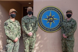 200625-N-IO414-1033 NAVAL SUPPORT ACTIVITY BAHRAIN (June 25, 2020) Ensign Jonathon Deering, left, Ensign Conor O'Donnell, center, and Ensign Michael Petty pose for a photo in front of U.S. Naval Forces Central Command's Naval Cooperation and Guidance for Shipping (NCAGS) headquarters. NCAGS serves as a communication link between merchant and military vessels and is made up entirely of U.S. Navy reservists, many of whom are professional merchant marines who leverage their civilian expertise and experience when they report for duty.