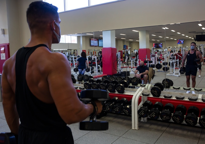 A man wearing a face mask watches his form in a mirror as he lifts dumbbells.