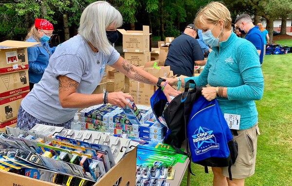 Camp Rosenbaum staff members Shelly Davison (left) helps Connie Opsal, Camp Rosenbaum Camp Director (right) fill backpacks for Operation Lemonade, in Portland, Ore., June 27, 2020.