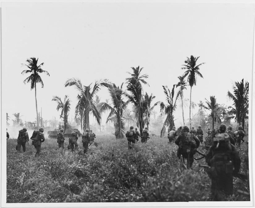 Several men and a tank push through an overgrown field near palm trees.
