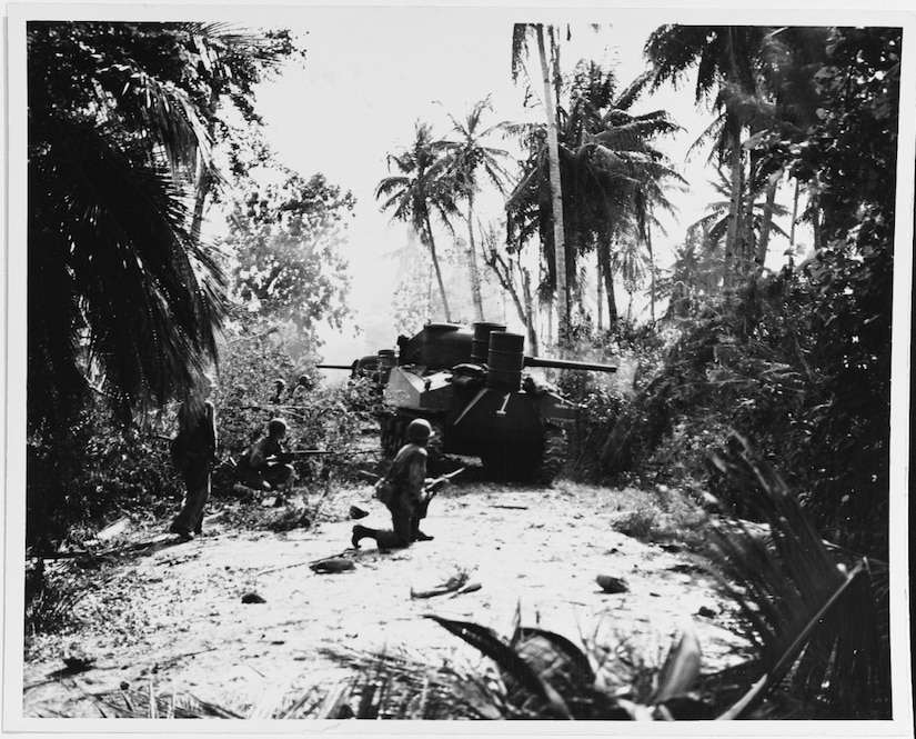 Men with rifles stand near a tank along a road in dense jungle.
