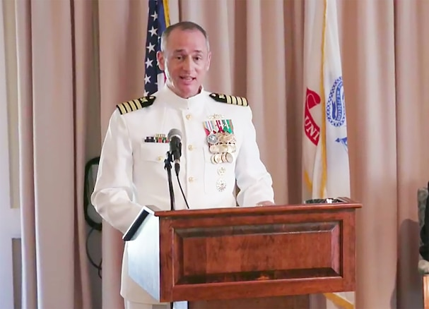 Navy Capt. Fred Dini stands behind a podium in his dress uniform as he speaks during a change of command ceremony.