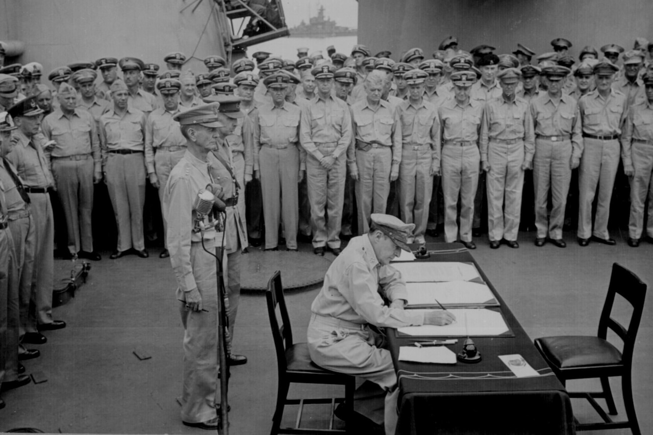 A military officer sits at a desk and signs papers while other officers stand around him.