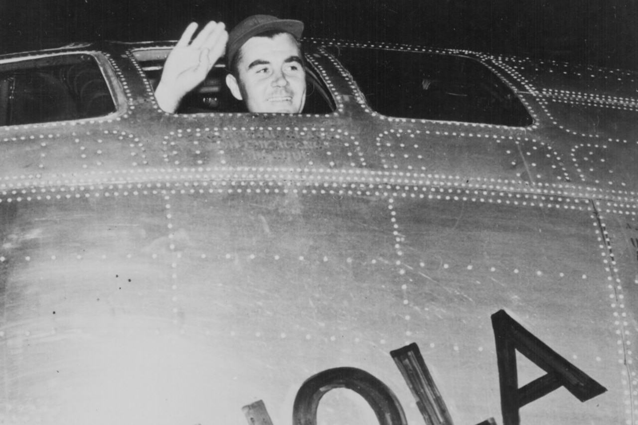 A man waves from the cockpit of a plane.